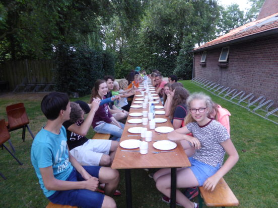 Lange biertafels werden ingezet om buiten te kunnen genieten van de zon en de barbecue.